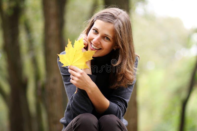 Schöne Frau mit einem Blumenstrauß der Ahornblätter stockfoto