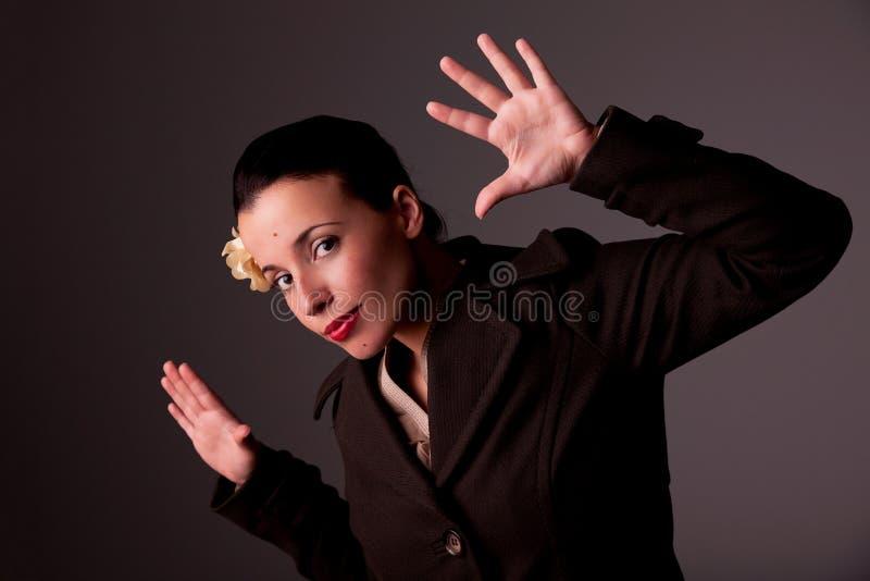 Schöne Frau mit einem coatand eine Blume im Haar lizenzfreie stockfotografie