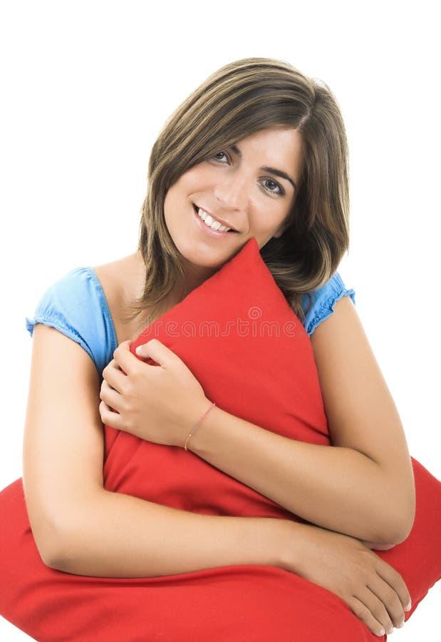 Schöne Frau mit einem weichen Kissen stockbild