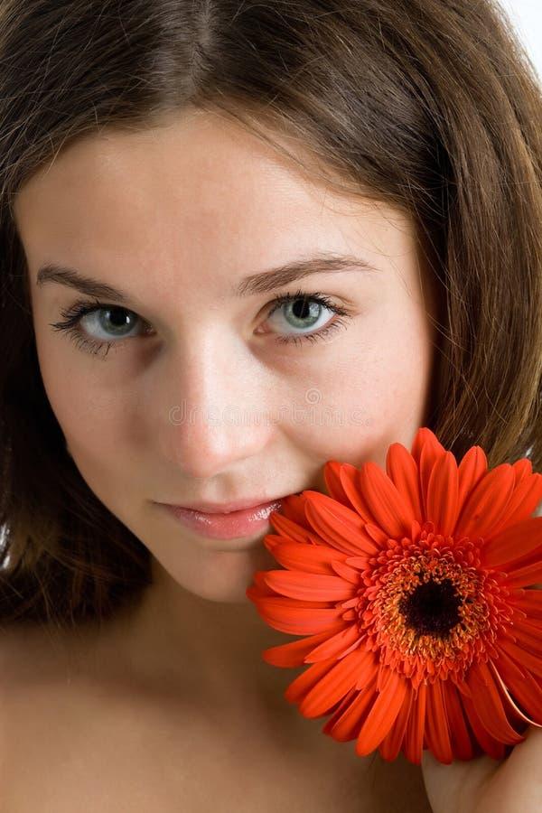 Schöne Frau mit einer hellen roten Blume stockfotos