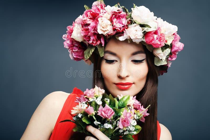 Schöne Frau mit einer Krone auf Kopf und Blumenstrauß stockfotografie