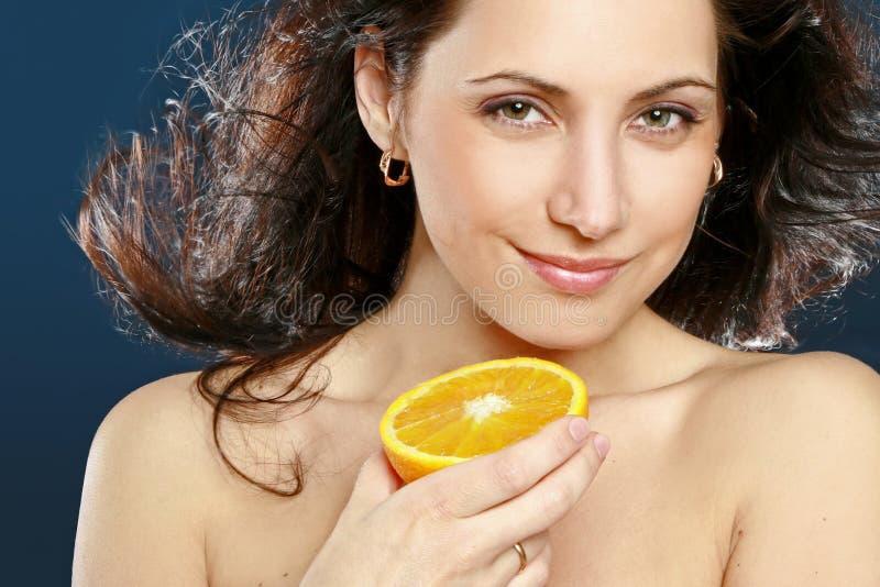Schöne Frau mit frischer Orange stockbild