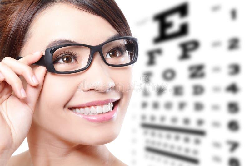 Frau mit Gläsern und Augentestdiagramm lizenzfreies stockbild