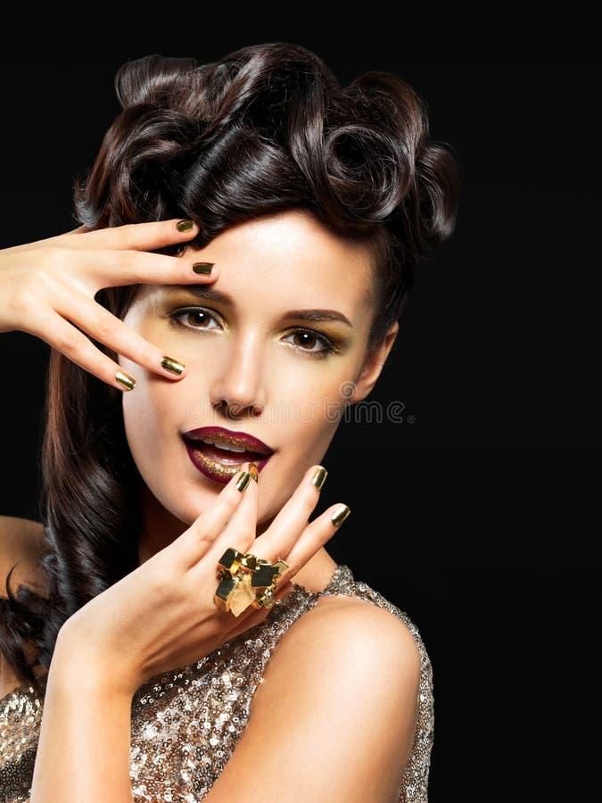 Schöne Frau mit goldenen Nägeln und Modemake-up stockfoto