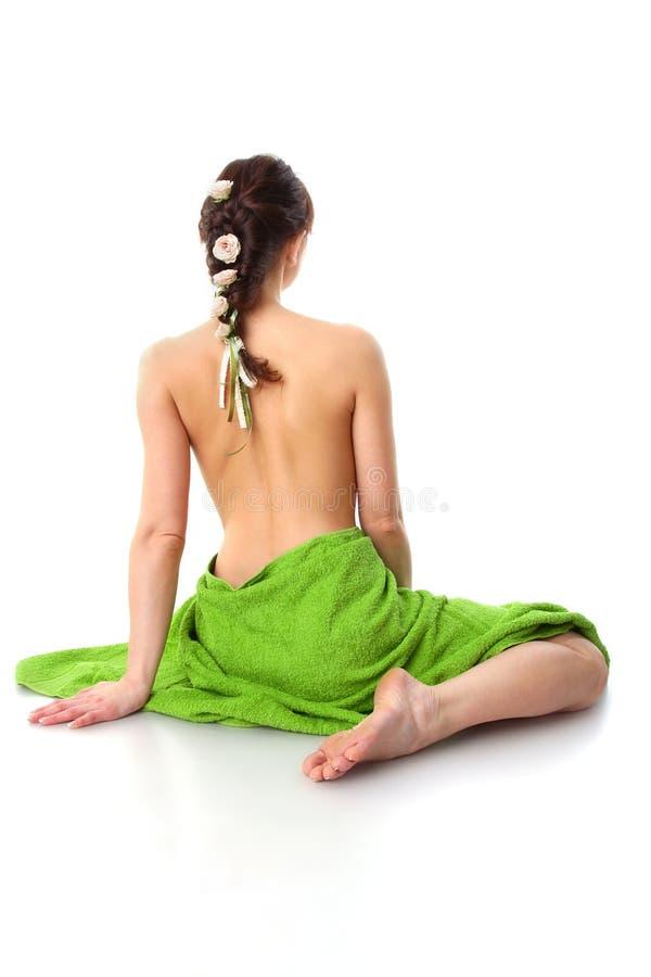 Schöne Frau mit grünen Badekurorttüchern auf Weiß lizenzfreie stockbilder