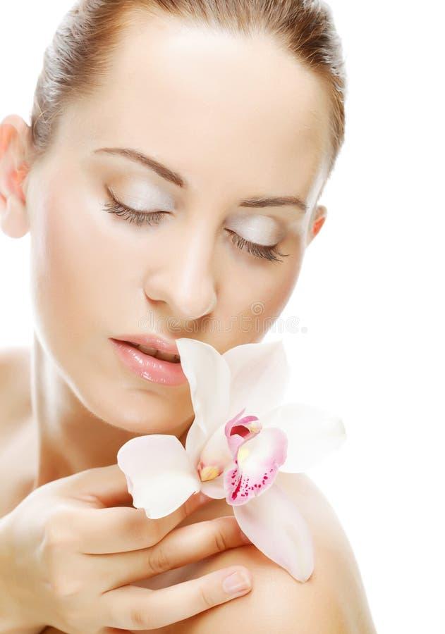 Schöne Frau mit Orchideeblume lizenzfreie stockfotos