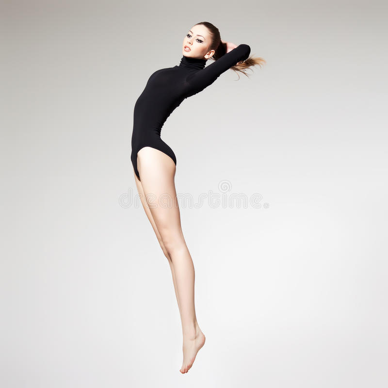 Schöne Frau mit perfekter dünner den springenden Karosserie und langen Fahrwerkbeinen - f lizenzfreie stockfotografie