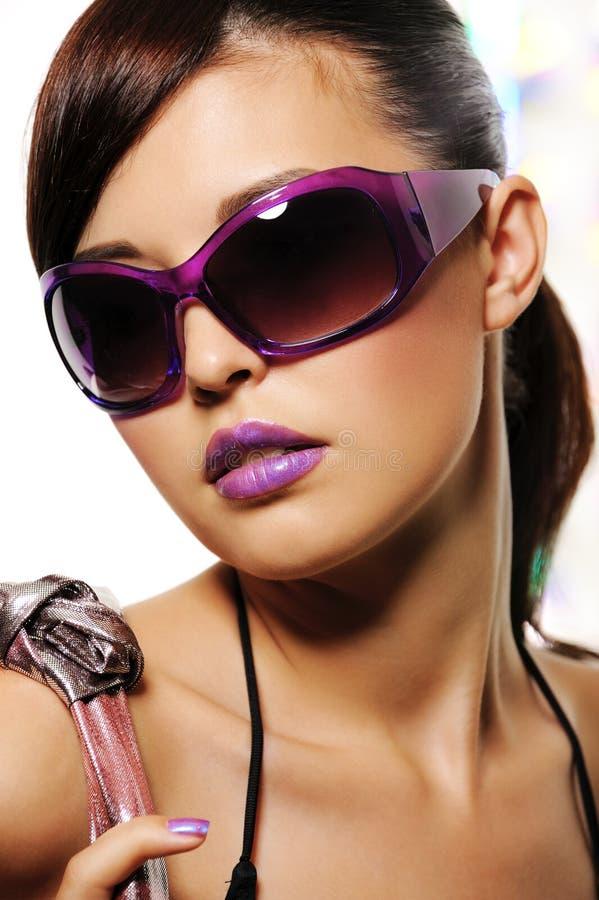 Schöne Frau mit purpurroten Art und Weisesonnenbrillen stockfotos