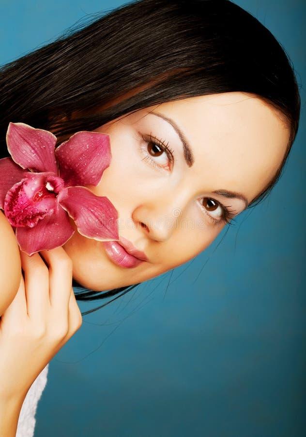 Schöne Frau mit rosafarbener Blume lizenzfreie stockfotografie