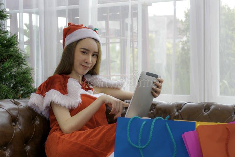 Schöne Frau mit Santa-Claus-Kleid auf Sofa sitzen und online mit Smartphone einkaufen mit farbenprächtiger Einkaufstasche zum Fei stockfotos