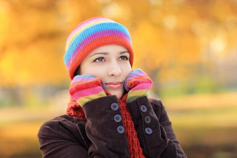 Schöne Frau mit Schutzkappe und Handschuhe im Herbst stockbild