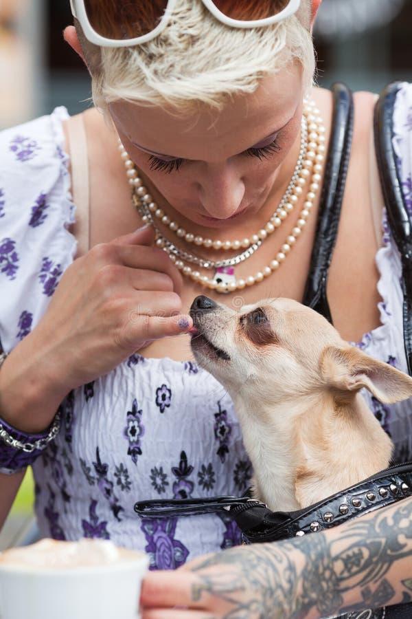 Schöne Frau mit Tätowierungen und einem Hund stockfoto