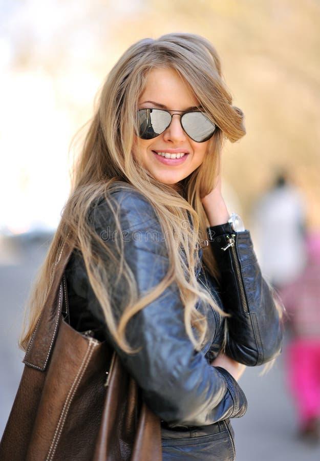 Schöne Frau mit tragender Sonnenbrille der Handtasche stockbild