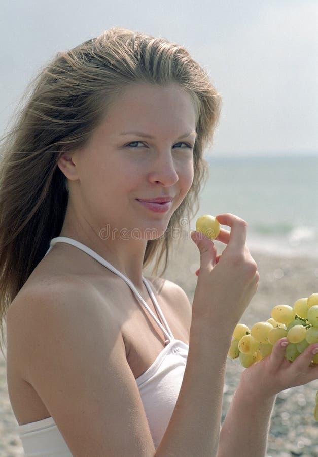 Schöne Frau mit Trauben auf Strand lizenzfreies stockbild
