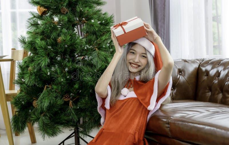 Schöne Frau trägt Santa-Claus-Kleid und hält die Geschenkkiste auf ihrem Kopf zum Feiern am WeihnaWeihnachtsfeiertag stockfotos