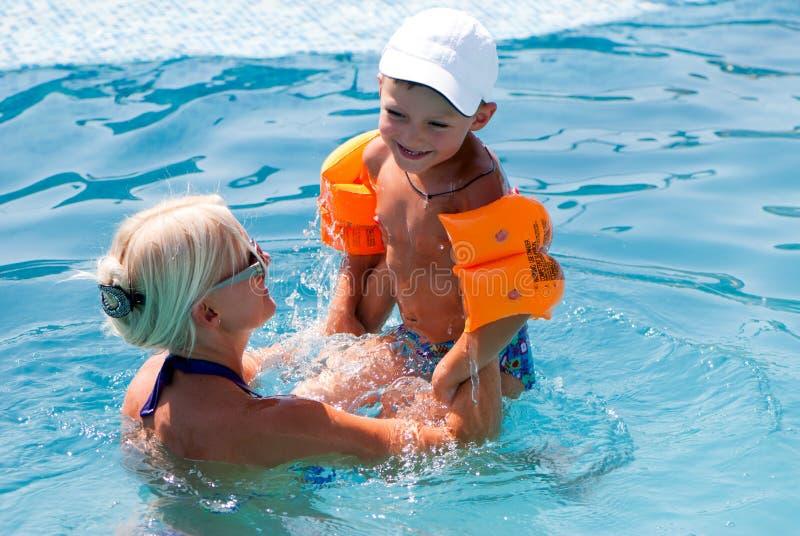 Schöne Frau und kleiner Junge badet im Pool lizenzfreie stockbilder