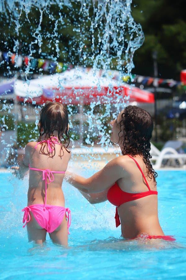 Schöne Frau und kleines Mädchen badet im Pool lizenzfreies stockfoto