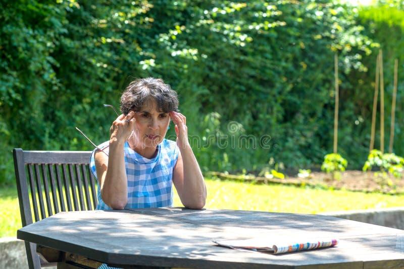 Schöne Frau von mittlerem Alter hat Kopfschmerzen im Garten lizenzfreie stockfotos