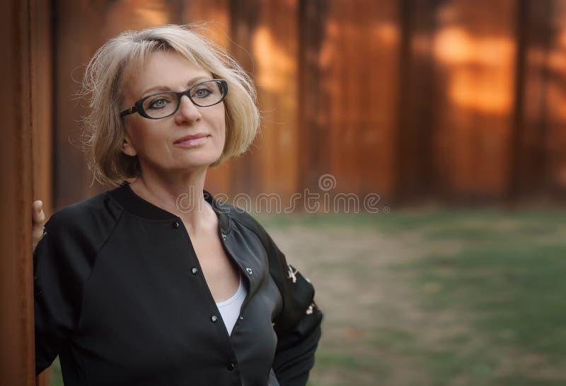 Schöne Frau von mittlerem Alter, welche die Wand im Park bereitsteht PH stockfoto