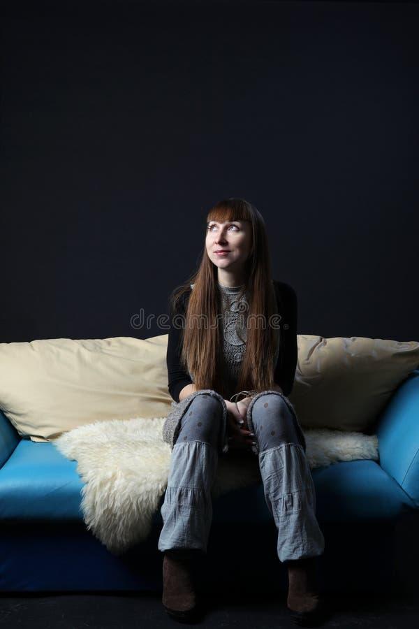 Schöne Frauen im grauen Kleid, das auf der Couch sitzt stockbilder