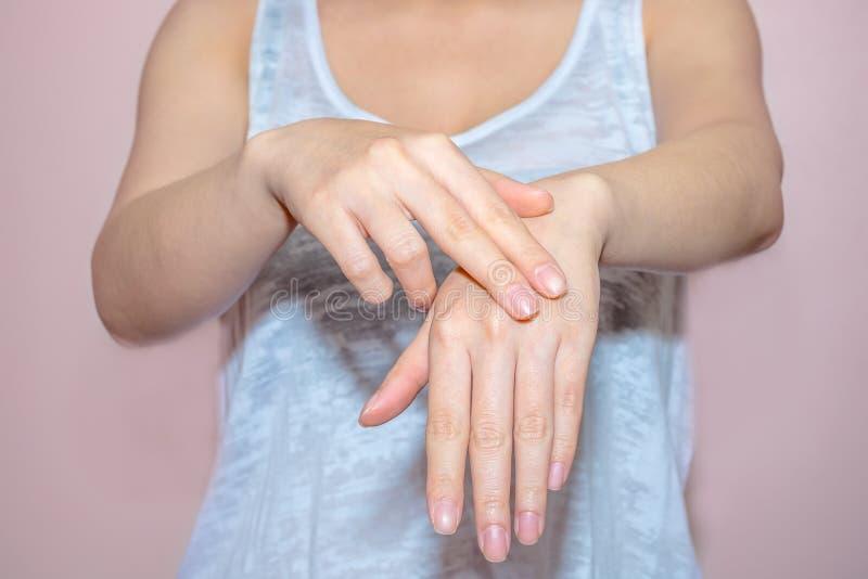 Schöne Frauenhände, die Sahne auftragen lizenzfreie stockfotos
