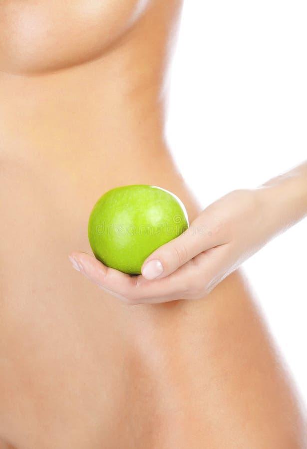 Schöne Frauenkarosserie und grüner Apfel. lizenzfreie stockbilder