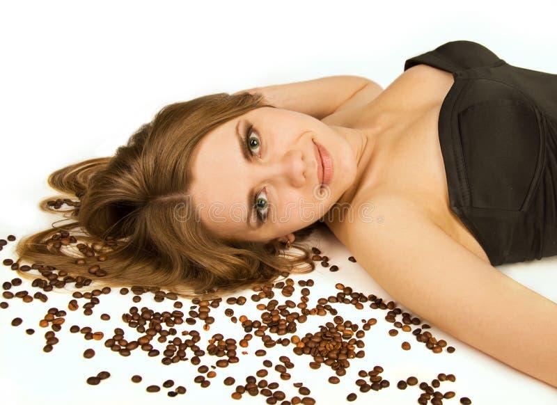 Schöne Frauenlüge auf Kaffeebohnen stockfotos