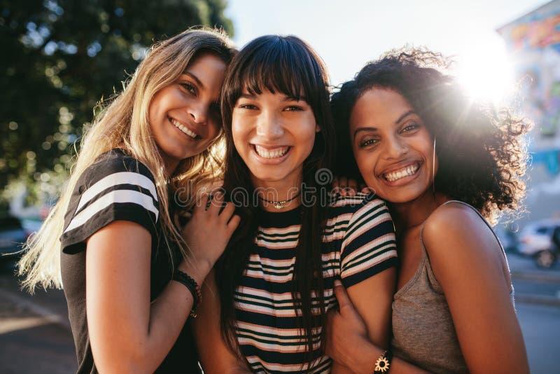Schöne Freundinnen, die zusammen glücklich schauen stockfoto