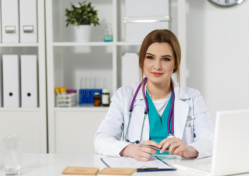 Schöne freundliche Ärztin, die am Funktionstisch sitzt lizenzfreies stockfoto