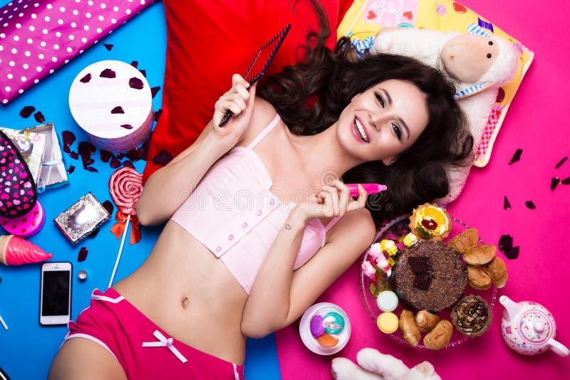 Schöne frische Mädchenpuppe, die auf den hellen Hintergründen umgeben durch Bonbons, Kosmetik und Geschenke liegt Modeschönheitsa stockbilder