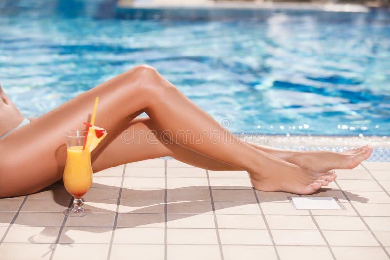 Schöne gebräunte Beine. Nahaufnahme von weiblichen Beinen und von Cocktail mit lizenzfreie stockfotografie