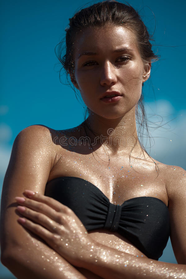 Schöne gebräunte Frau auf dem Strand und dem Ein Sonnenbad nehmen Funkeln auf ihrem perfekten dünnen Körper lizenzfreie stockbilder