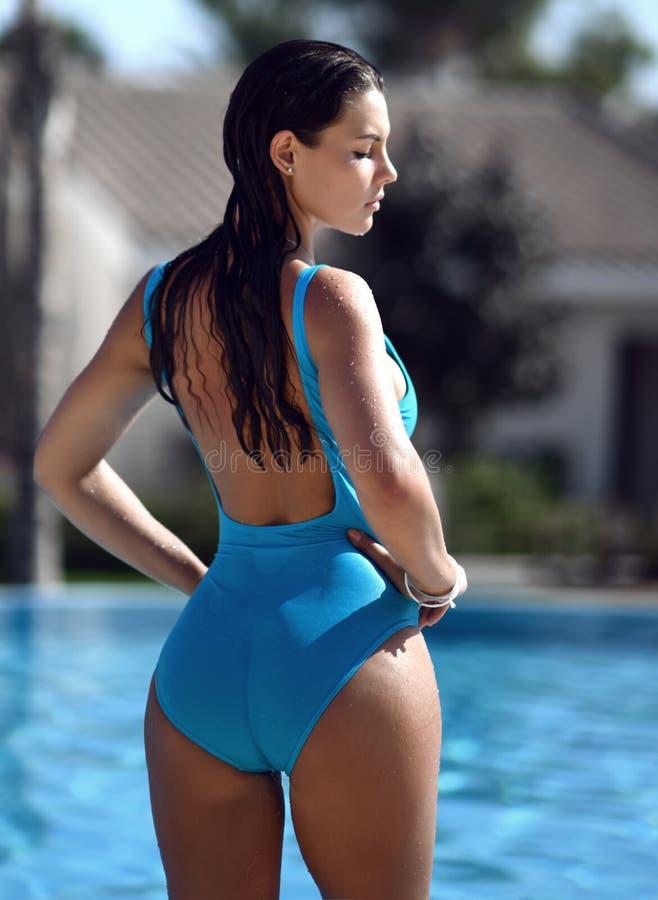 Schöne gebräunte Frau in der blauen Badebekleidung, die im Swimmingpoolbadekurort nahe teurem Landhaus am heißen Sommertag sich e stockbild