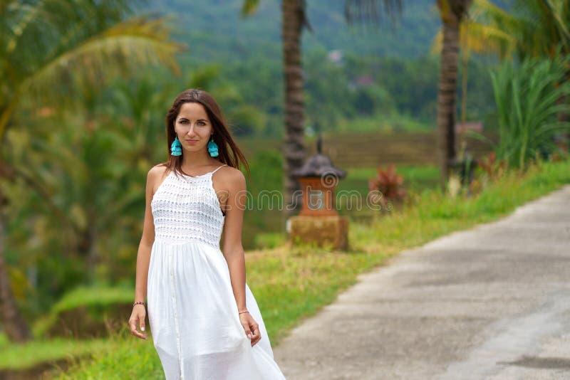 Sch?ne gebr?unte Frau im wei?en Kleid, das Stellung auf der Stra?e aufwirft Im Hintergrund sind Palmen und andere tropische Veget stockbild