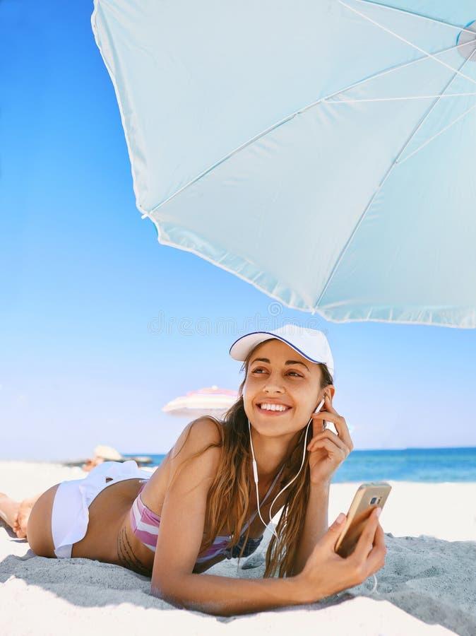 Schöne gebräunte lächelnde Frau liegt auf dem Strand auf einem weißen Sand und entspannt sich und hört Musik vom Telefon mit stockfoto