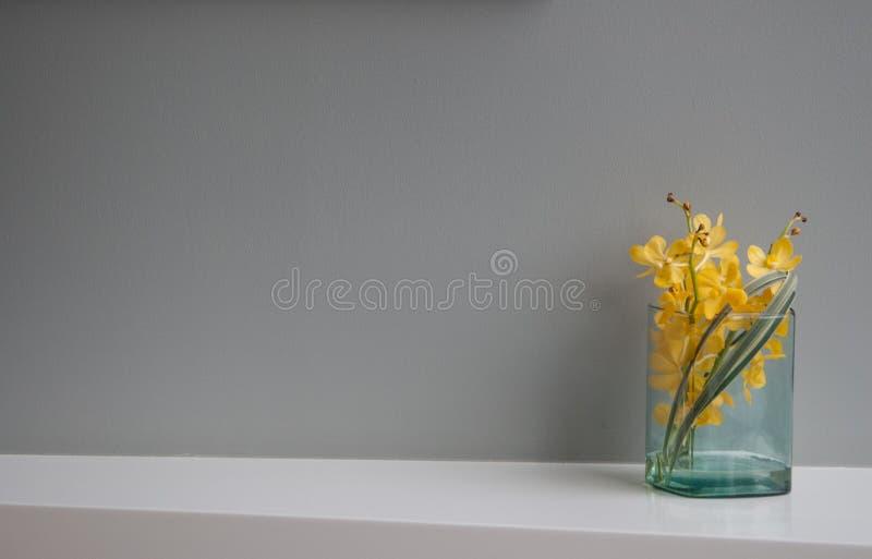 Schöne gelbe Blume im Grasvase auf dem Tisch und im Grau lizenzfreie stockfotografie