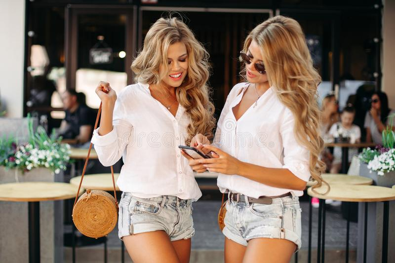 Schöne gelockte Zwillinge, die Smartphone halten, nahe Restaurant draußen zu stehen lizenzfreies stockbild