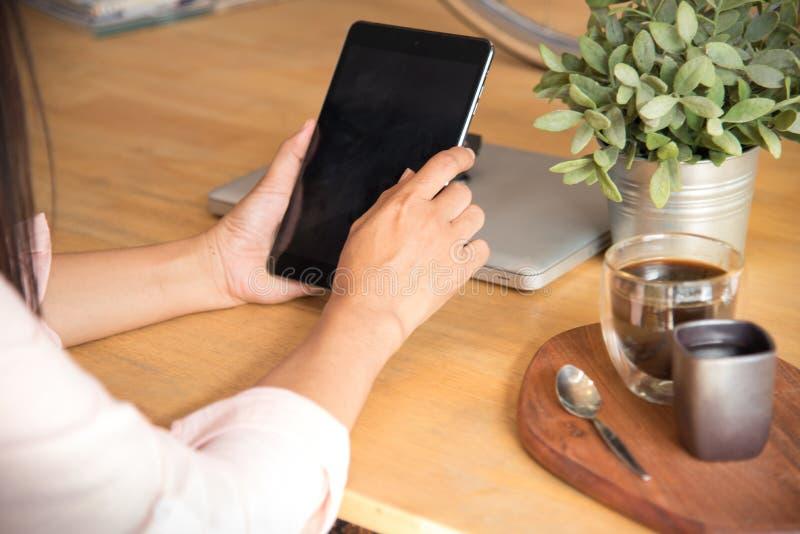 Schöne Geschäftsberufstätige frau unter Verwendung Ipad beim Arbeiten mit Laptop und Ablesen des Berichts, Diagramme stockbild