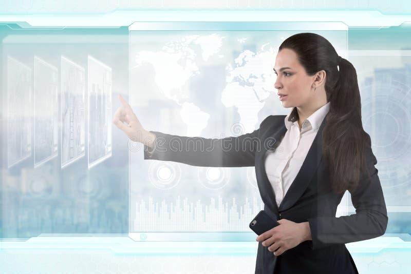Schöne Geschäftsdame arbeitet mit virtueller grafischer Schnittstelle Futuristisches Büro lizenzfreie stockfotos