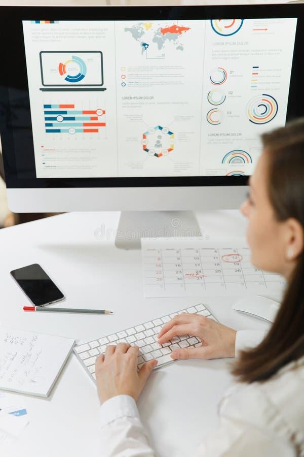 Schöne Geschäftsfrau in der Klagen- und Glasfunktion am Computer mit Dokumenten im hellen Büro lizenzfreie stockfotos