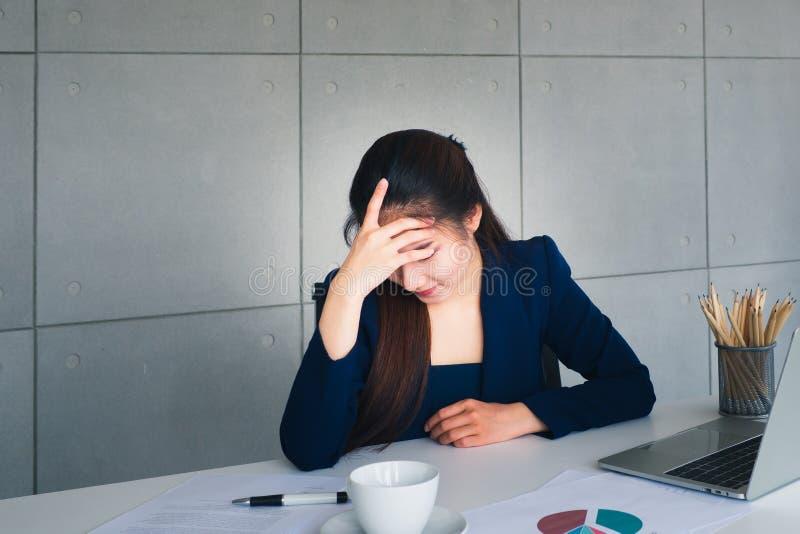 Schöne Geschäftsfrau des asiatischen langen Haares in der Marineblau-Klagenbelastung mit Arbeit util-Kopfschmerzen in ihrem Büro  lizenzfreie stockfotografie