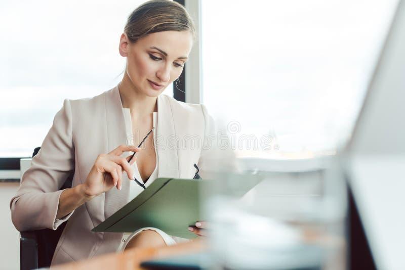 Schöne Geschäftsfrau, die eine Datei in ihrem Büro liest stockbilder
