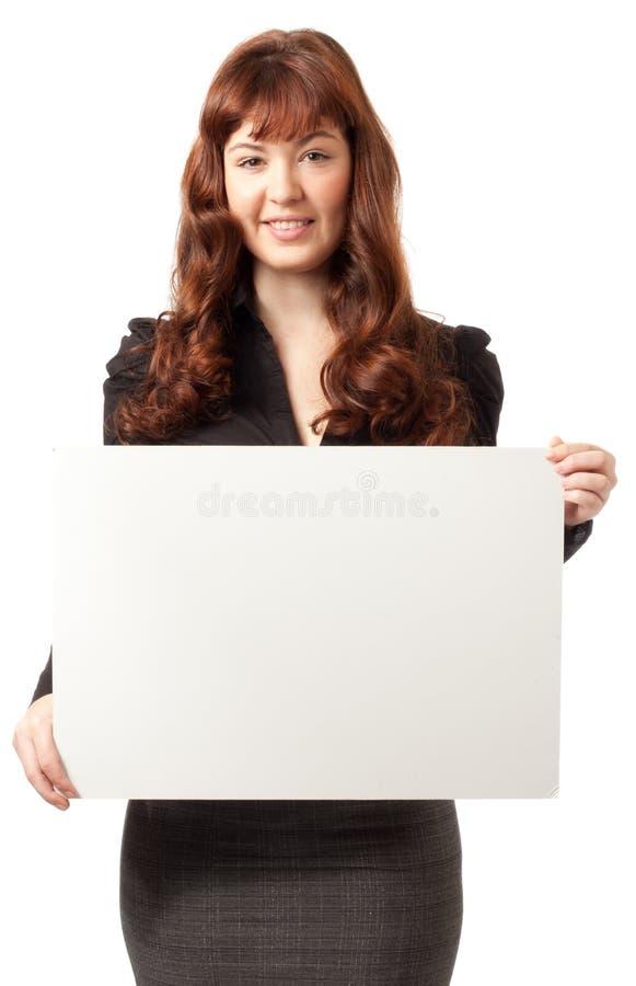 Schöne Geschäftsfrau, die eine unbelegte Anschlagtafel anhält lizenzfreies stockfoto