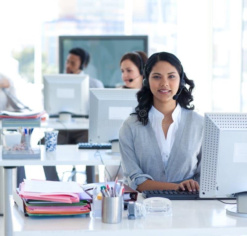 Schöne Geschäftsfrau, die in einem Kundenkontaktcenter arbeitet stockfotografie