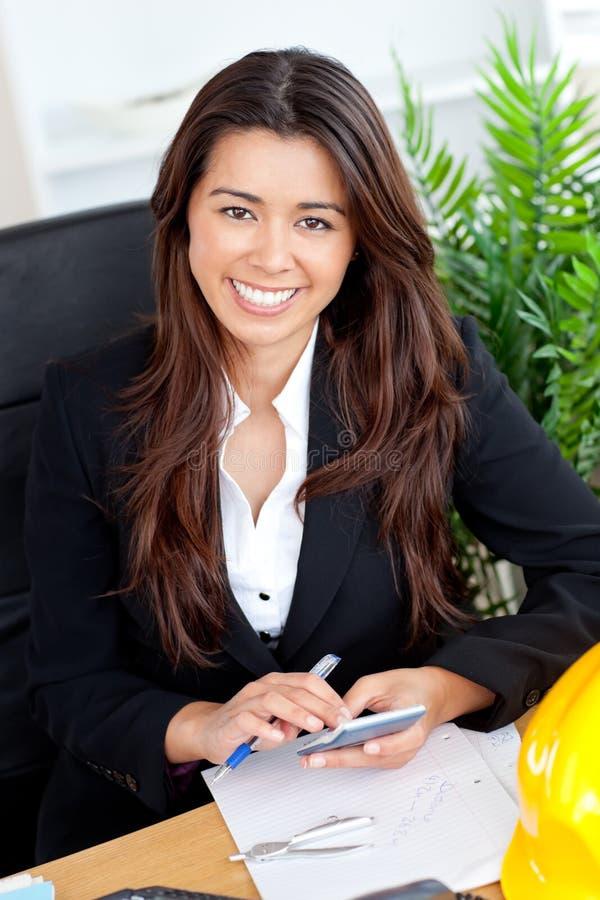 Schöne Geschäftsfrau, die einen Rechner verwendet stockfotografie