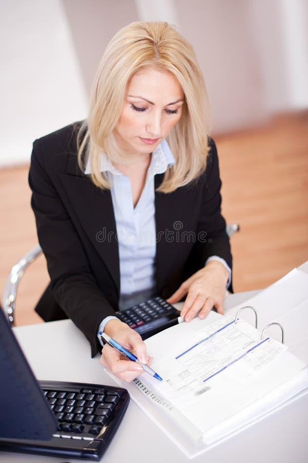 Schöne Geschäftsfrau, die Finanzen tut stockfoto