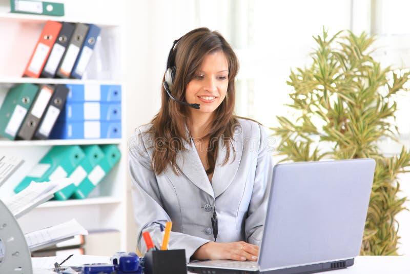 Schöne Geschäftsfrau, die an ihrem Schreibtisch mit arbeitet stockfotos