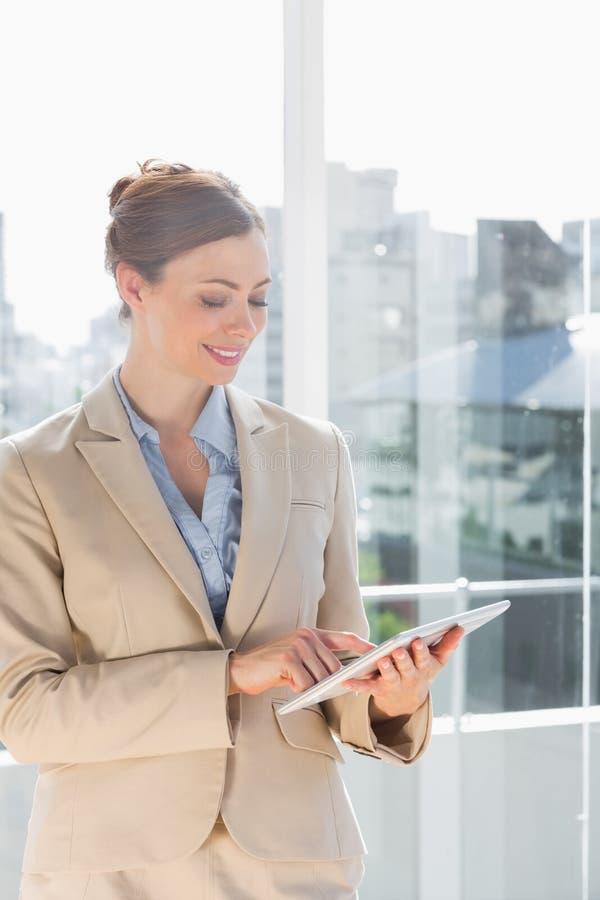 Schöne Geschäftsfrau, die ihren Tabletten-PC verwendet stockfotografie