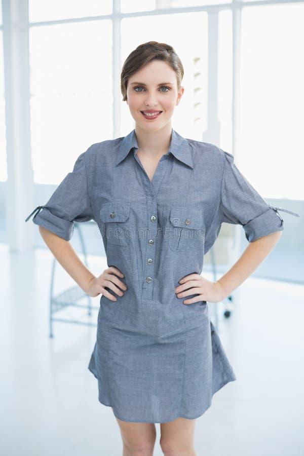 Schöne Geschäftsfrau, die im Büro mit den Händen auf Hüften aufwirft stockfoto