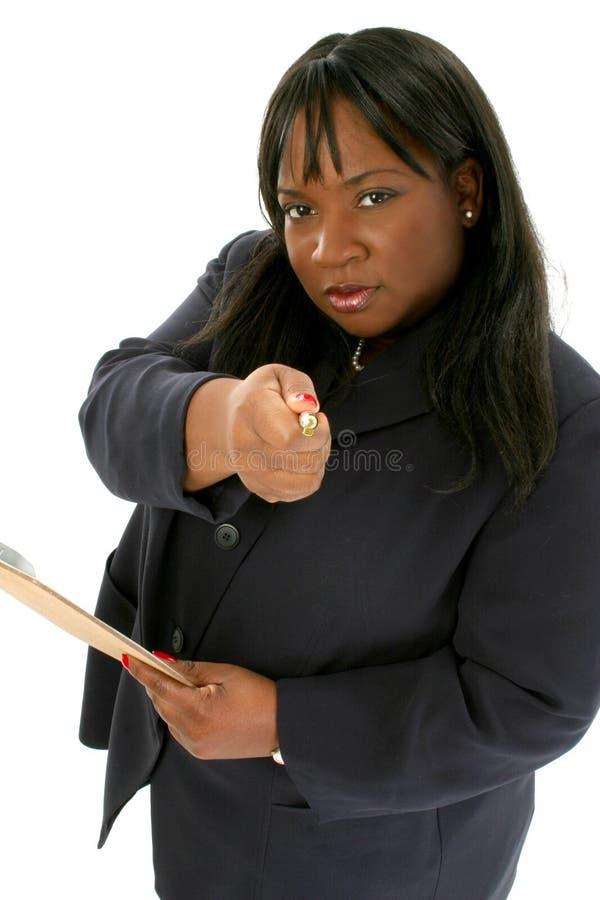 Schöne Geschäftsfrau, die mit Feder zeigt stockfoto